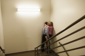 Young business couple kissing in office stairwell
