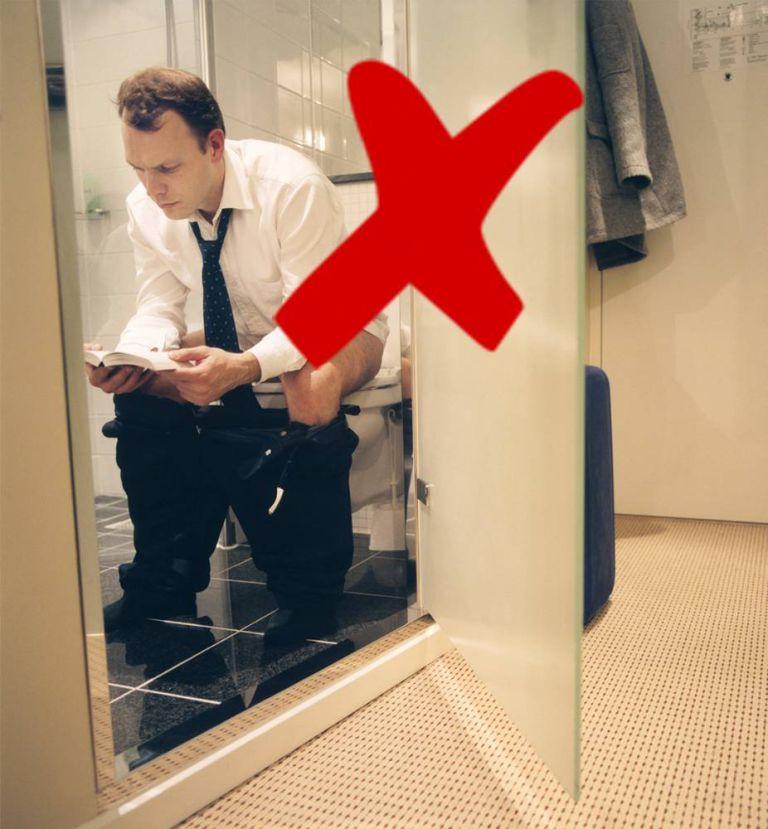 Man Reading Book on Toilet